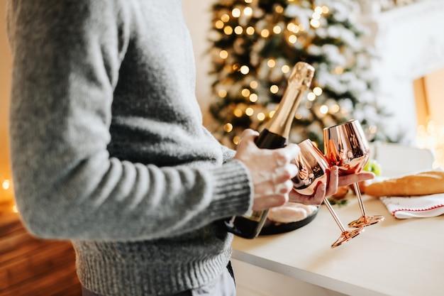 Hombre sujetando copas y champaña Foto gratis