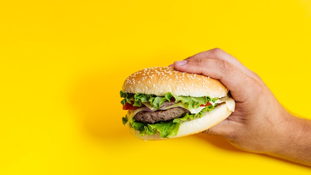 Hombre sujetando hamburguesa delante de fondo amarillo Foto gratis