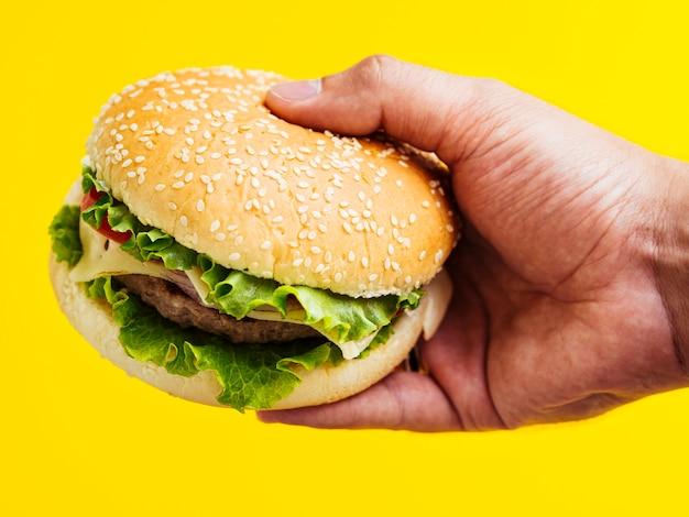 Hombre sujetando una hamburguesa con queso con semillas Foto gratis
