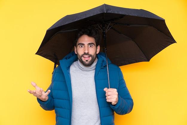 Hombre sujetando un paraguas sobre pared aislada Foto Premium