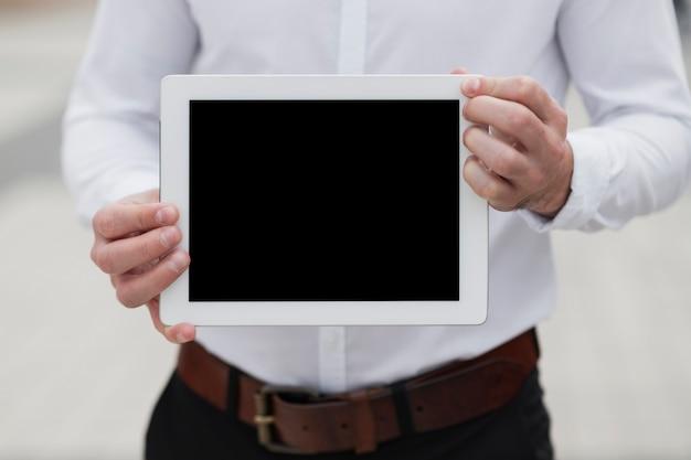 Hombre sujetando vista frontal de maqueta de ipad Foto gratis