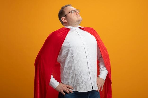 Hombre de superhéroe adulto seguro en capa roja con gafas manteniendo las manos en la cintura mirando al lado aislado en la pared naranja Foto gratis