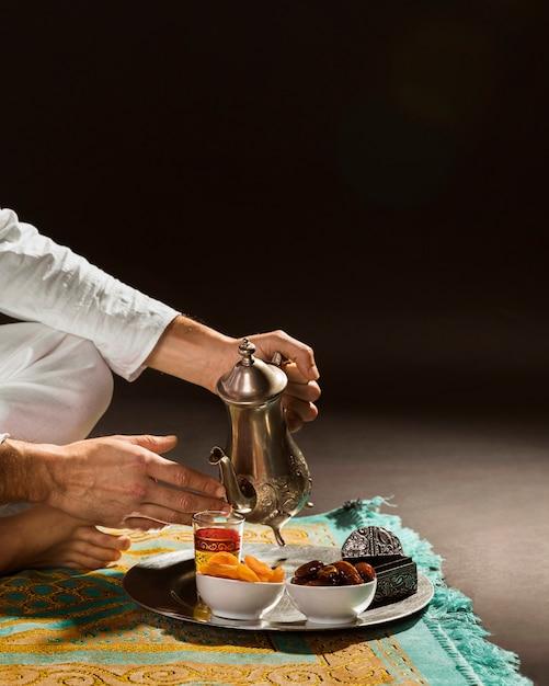Hombre en té blanco vertiendo en pequeña vista frontal de la taza Foto gratis