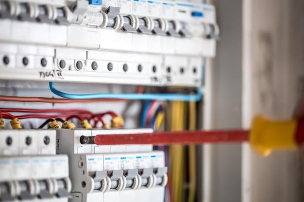 Hombre, un técnico eléctrico que trabaja en una centralita con fusibles. instalación y conexión de equipos eléctricos. de cerca. Foto gratis