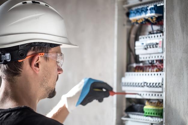 Hombre, un técnico eléctrico que trabaja en una centralita con fusibles. instalación y conexión de equipos eléctricos. Foto gratis