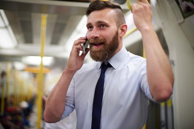 Hombre con teléfono móvil en el metro Foto gratis