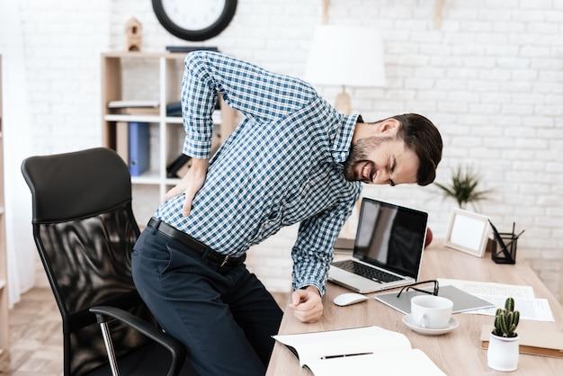 El hombre tiene dolor de espalda. él mantiene sus manos en la cintura. Foto Premium