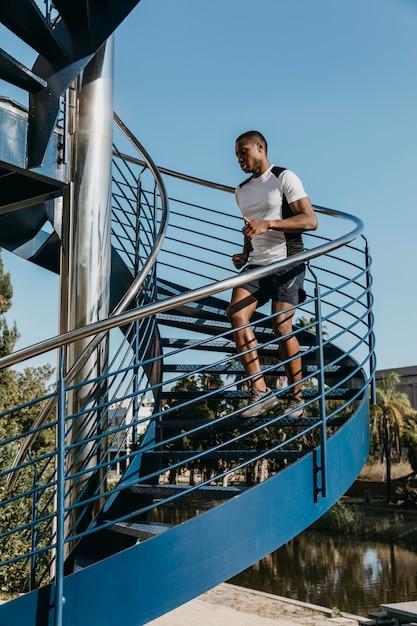 Hombre de tiro completo corriendo en las escaleras Foto gratis
