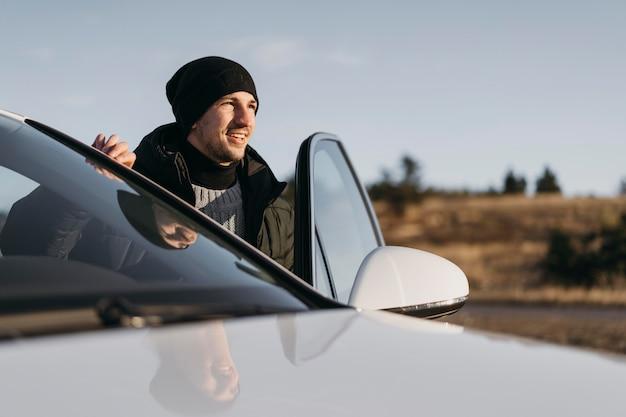 Hombre de tiro medio saliendo del coche Foto gratis