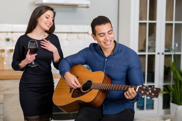 Hombre tocando una canción en la guitarra para su novia Foto gratis