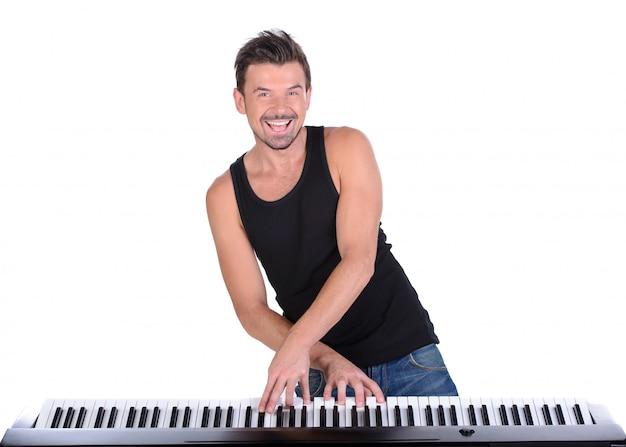 El hombre está tocando el piano digital y la sonrisa. Foto Premium