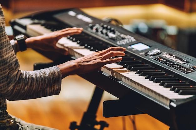 Hombre tocando sintetizador de teclado musical electrónico por manos. Foto Premium