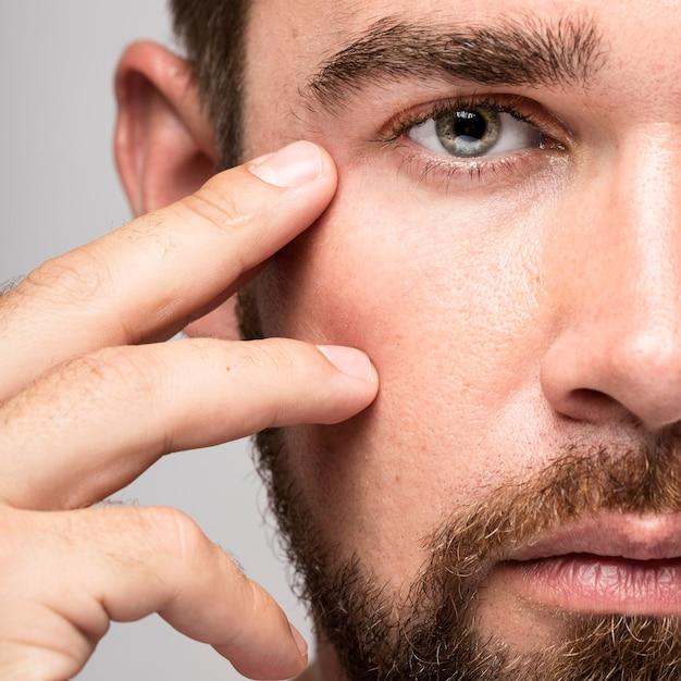 Hombre tocando su rostro de cerca Foto gratis