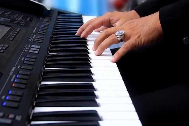 Un hombre tocando las teclas del teclado del piano Foto Premium