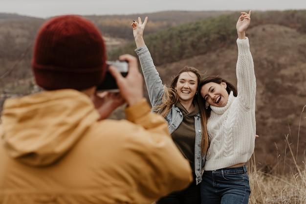 Hombre tomando fotos de mujeres en la naturaleza Foto gratis