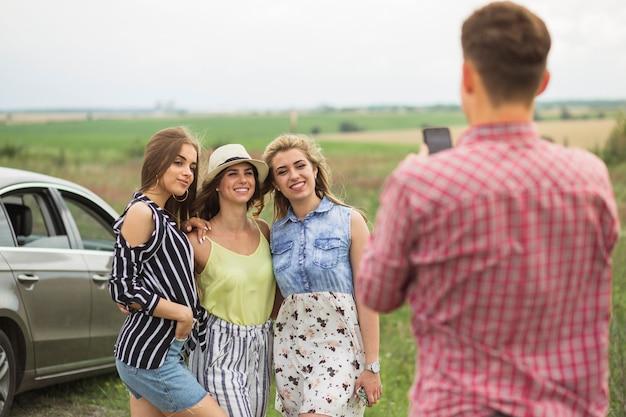 Hombre tomando fotos de tres amigas en el teléfono móvil Foto gratis