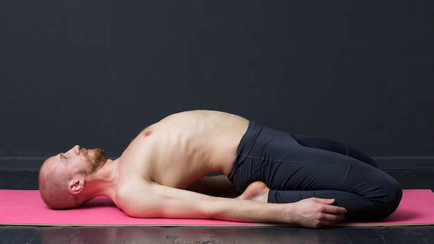El hombre con el torso desnudo está tendido sobre la estera, doblando la espalda Foto Premium