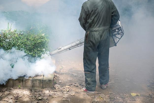 El hombre trabaja empañándose para eliminar el mosquito y prevenir la propagación del dengue Foto Premium