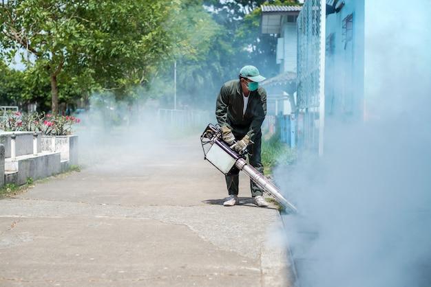 El hombre trabaja empañándose para eliminar el mosquito para prevenir la propagación de la fiebre del dengue y el virus zika Foto Premium