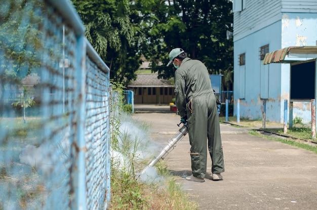 El hombre trabaja empañándose para eliminar el mosquito para prevenir la propagación de la fiebre del dengue Foto Premium