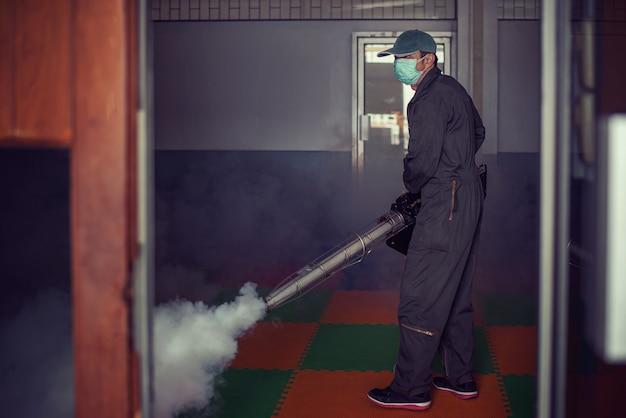 El hombre trabaja empañándose para eliminar el mosquito Foto Premium