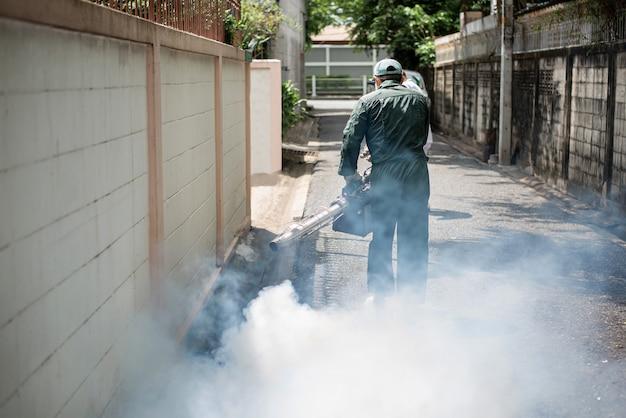 El hombre trabaja con nebulización, deshacerse de los mosquitos para detener la propagación de la fiebre del dengue Foto Premium
