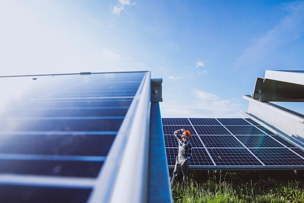 Hombre trabajador en el campo junto a los paneles solares. Foto gratis