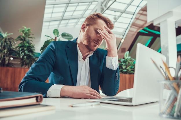 El hombre trabajador en traje está cansado en el escritorio en la oficina. Foto Premium