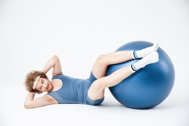 Hombre trabajando abdominales con piernas en pelota de ejercicios Foto gratis