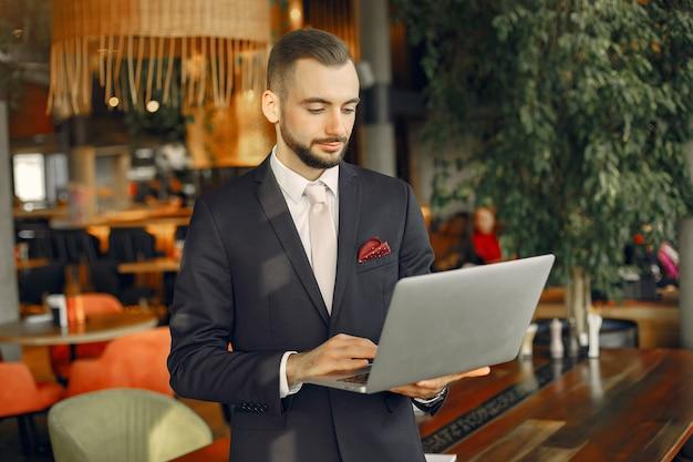 Hombre trabajando con una computadora portátil en la mesa Foto gratis
