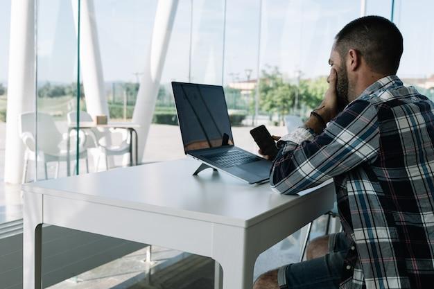 Hombre trabajando frente a la computadora portátil y con un móvil en la mano en un espacio de trabajo Foto gratis