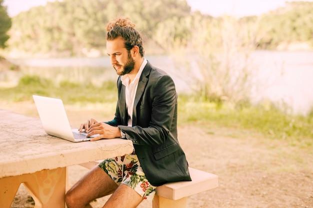 Hombre trabajando con laptop contra paisaje pintoresco Foto gratis