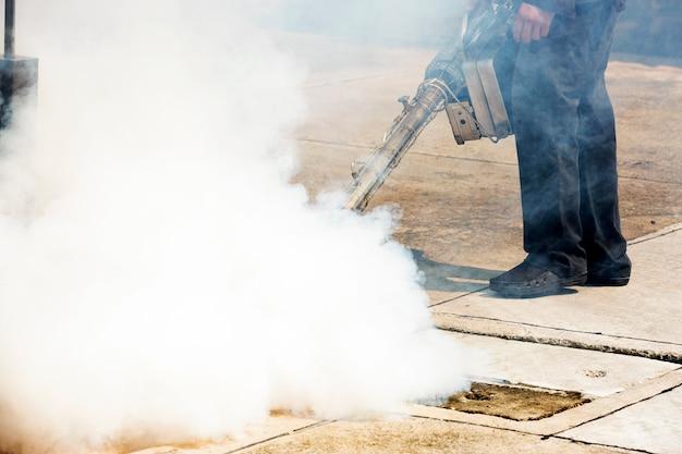 Hombre trabajando con una máquina de humo en la boca de inspección para el control de plagas Foto Premium
