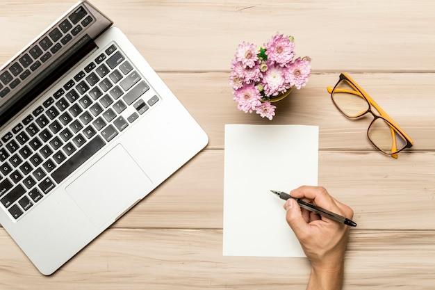 Hombre trabajando en mesa con hoja de papel vacía y cuaderno Foto gratis