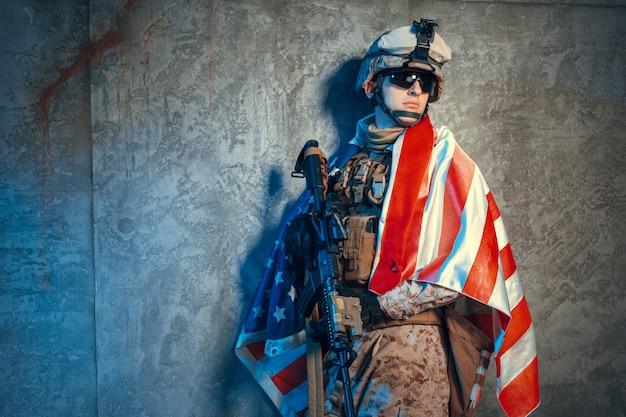 Hombre traje militar un soldado mercenario en los tiempos modernos con bandera estadounidense en estudio Foto Premium
