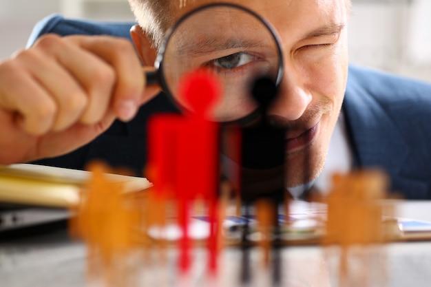 El hombre en traje mira a través de la lupa en estatuillas closeup Foto Premium