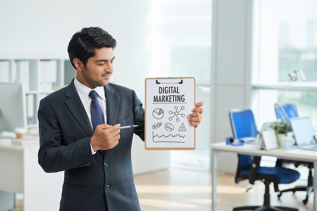 Hombre en traje de pie en la oficina con portapapeles y apuntando al cartel con palabras Foto gratis