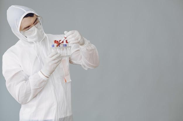 Hombre con traje protector y gafas trabajando en laboratorio Foto gratis