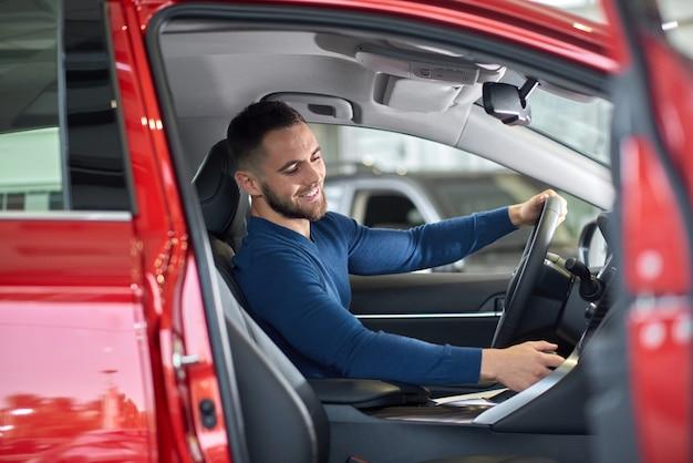 Hombre trigueno hermoso que se sienta en coche rojo con la puerta abierta. Foto Premium
