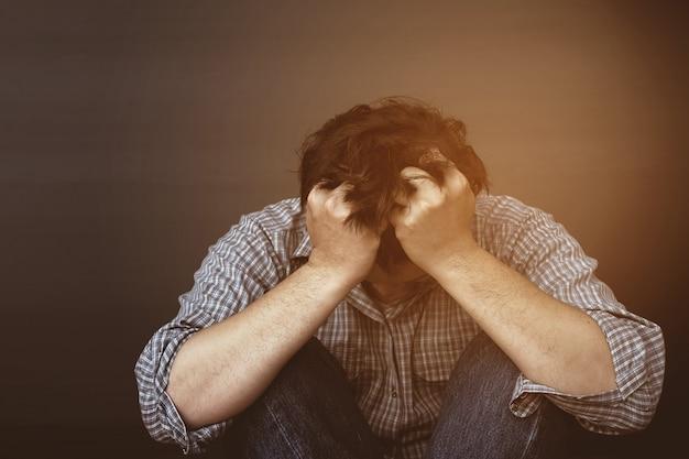 Hombre triste sosteniendo la cabeza con la mano Foto gratis
