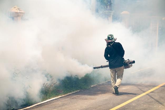 El hombre usa la máquina de mosquitos de fumigación Foto Premium