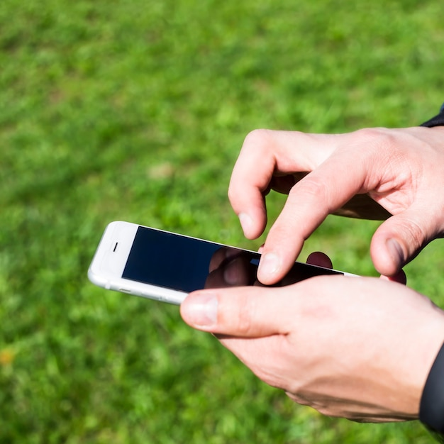 Un hombre usa un teléfono inteligente al aire libre. Foto Premium