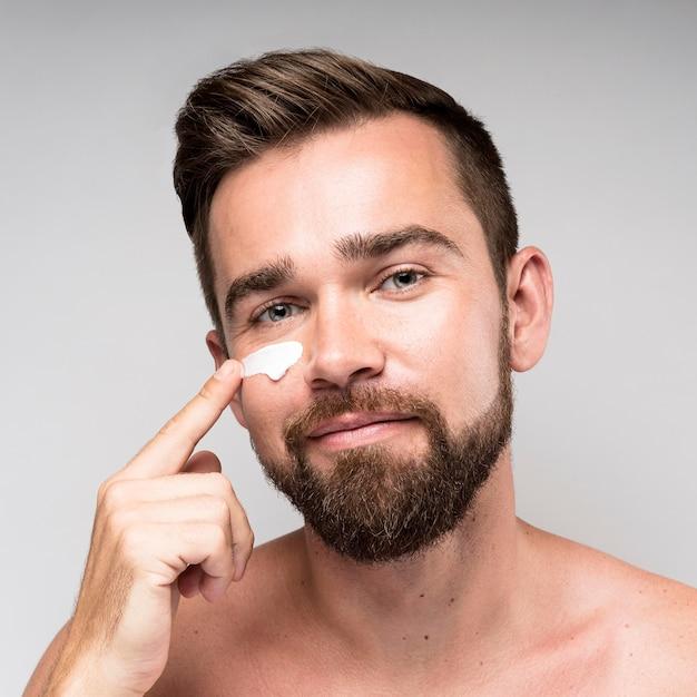 Hombre usando crema facial Foto gratis