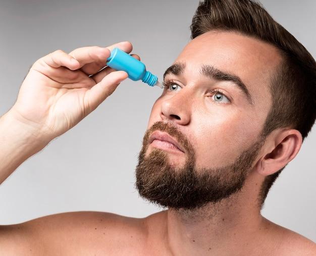 Hombre usando gotas para los ojos Foto gratis