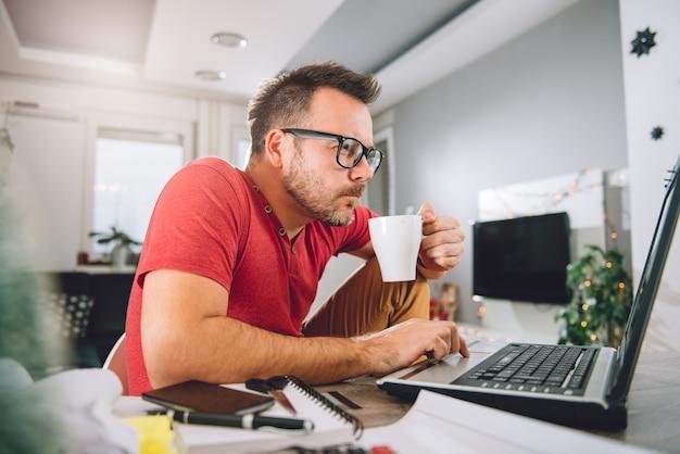 Hombre usando laptop y tomando café Foto Premium
