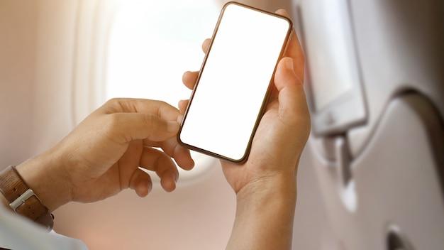 Hombre usando la pantalla en blanco del teléfono inteligente en el avión Foto Premium