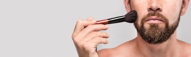 Hombre usando un pincel de maquillaje en la cara con espacio de copia Foto gratis