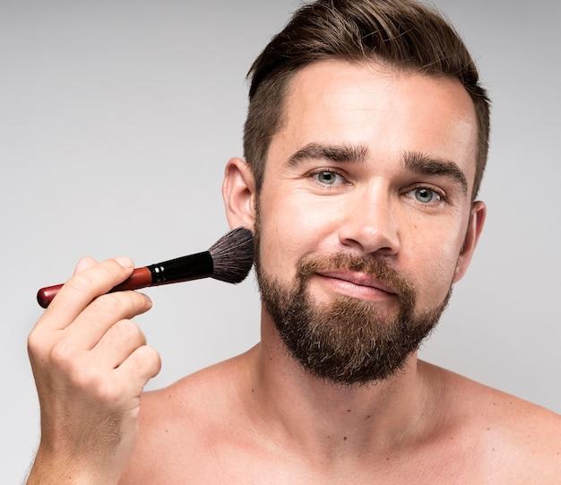 Hombre usando un pincel de maquillaje en la cara Foto gratis