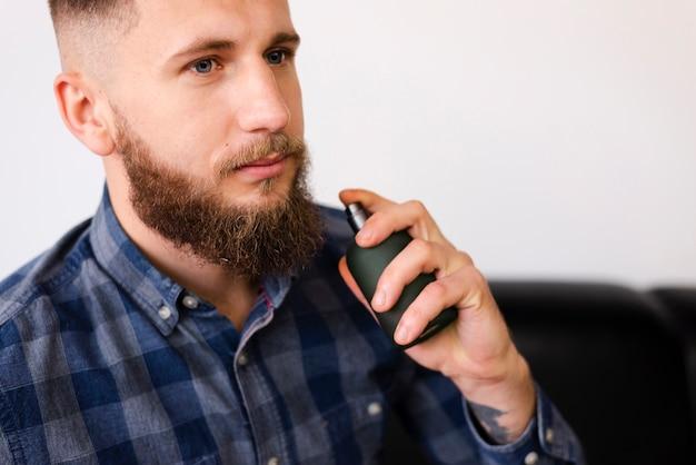 Hombre usando un spray después de cortarse el pelo Foto gratis