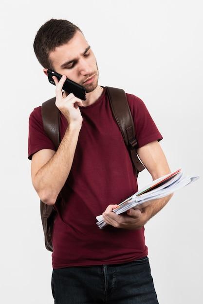 Hombre usando su teléfono y mirando sus notas Foto gratis
